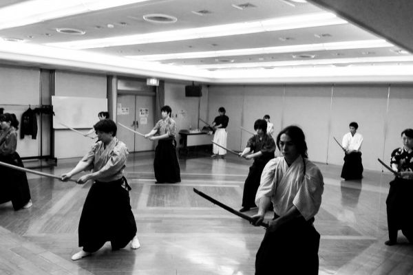 People in traditional Japanese clothes, holding katana swords